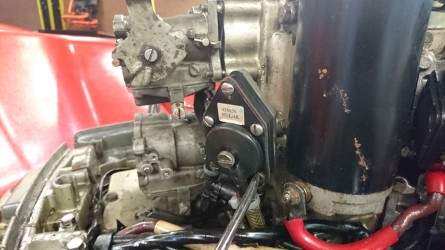 This is the fuel pump. It uses a diaphragm which pumped using compression from inside the engine (there is a small hole in the casing behind the pump where it gets this pressure from). Remove the two bottom screws only and the pump should come away. There is a gasket behind the pump, save this for reuse when reassembling.