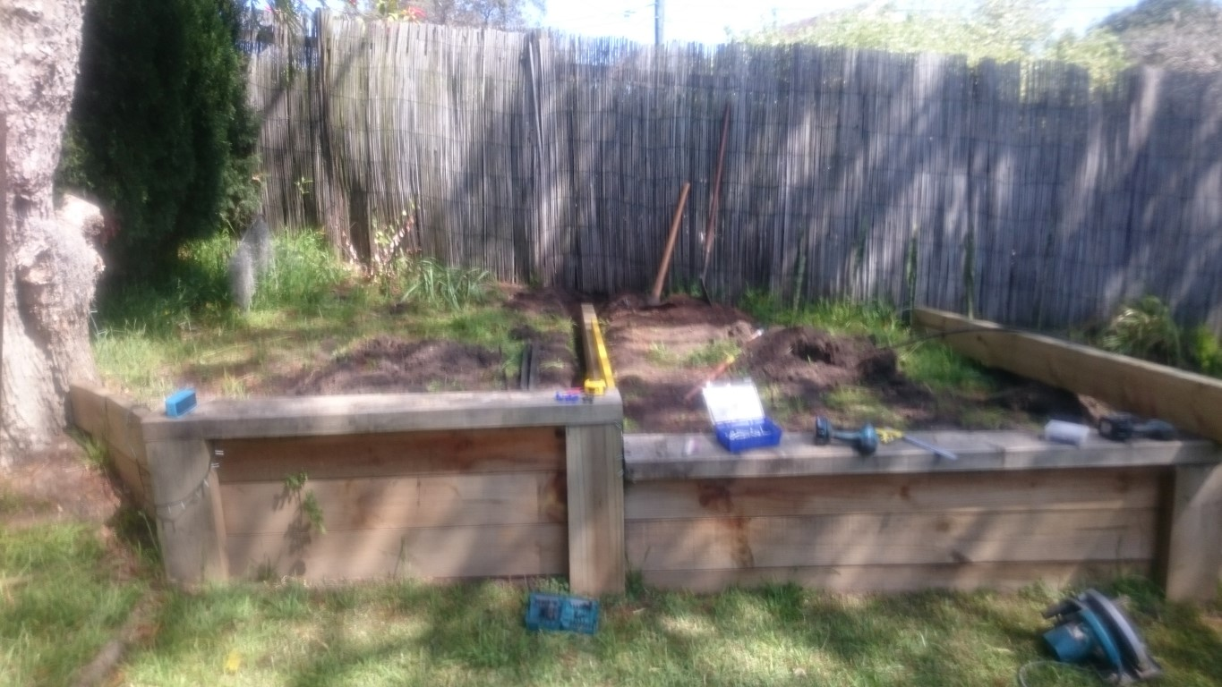 The existing retaining wall was stepped to follow the slope of the land. This meant that the whole vege patch was on a slope, which looked terrible and wasn't practical. You can see the new sleepers we were installing to partition the box in to 3.